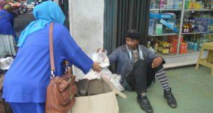 PWI Padang Panjang membagikan pabukoan kepada salah seorang tukang sol sepatu.( foto : PWI)