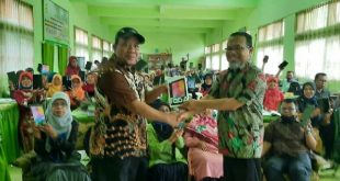 Kepala SMPN 1 Harau, M. Yusuf Lubis menyerahkan smartphone jenis tablet dan paket data pada para guru di sekolah tersebut