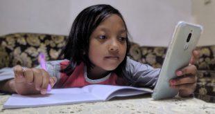 Seorang bocah sedang serius mengikuti belajar daring